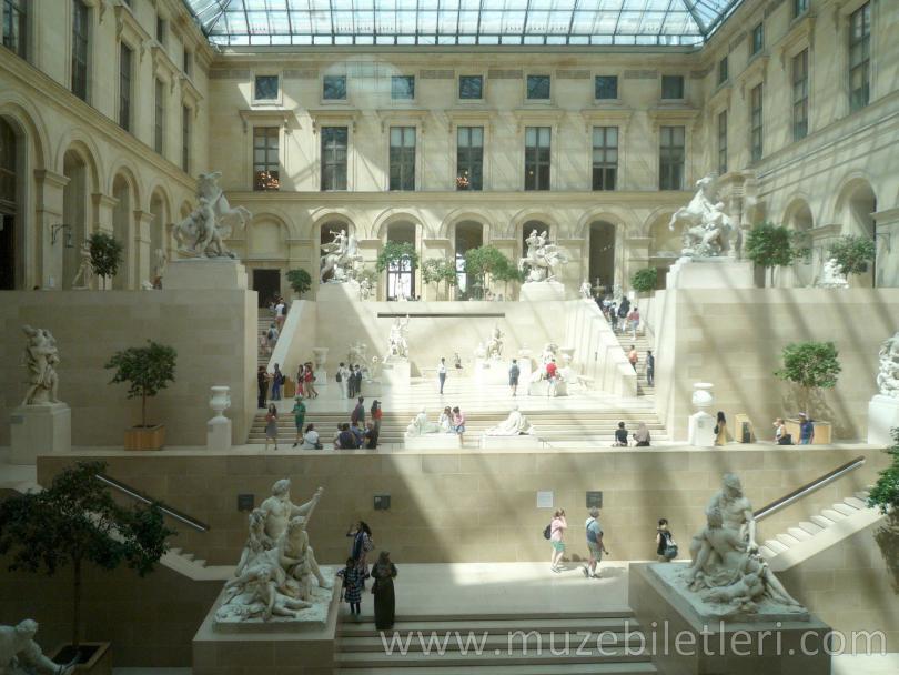 Louvre Müzesi ziyaretçileri heykelleri geziyor.