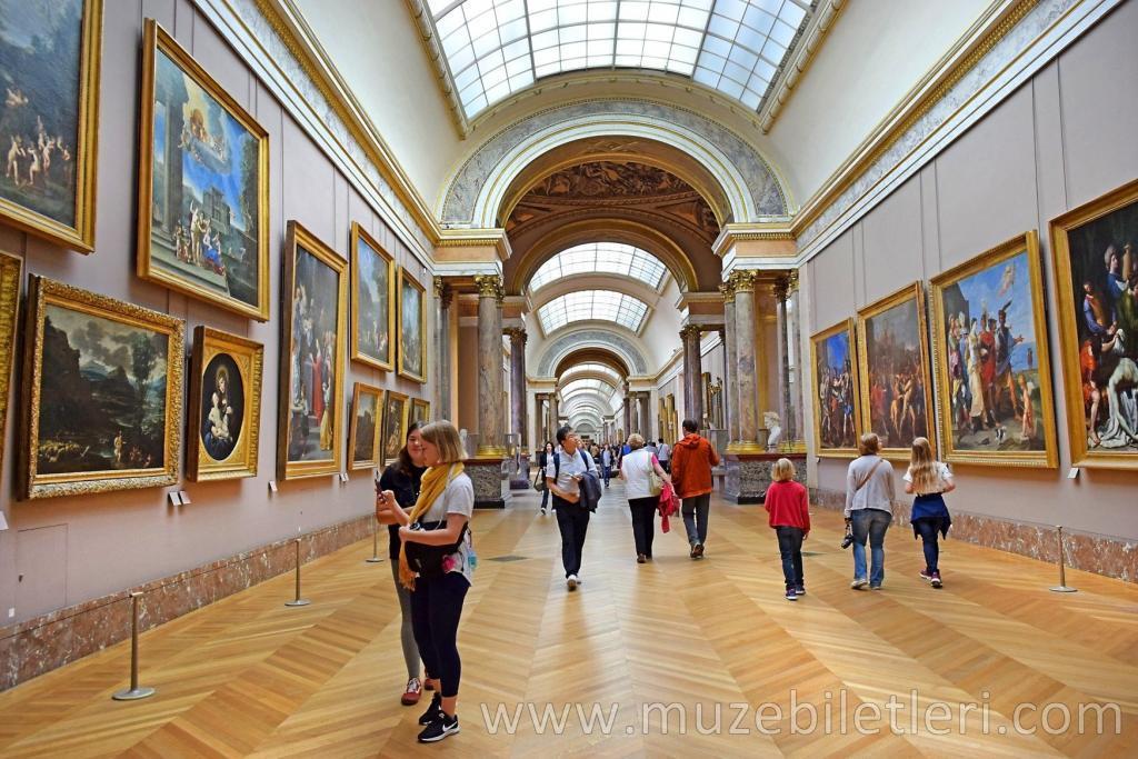 Louvre Müzesi'nin ziyaretçileri resim galerilerini geziyor.